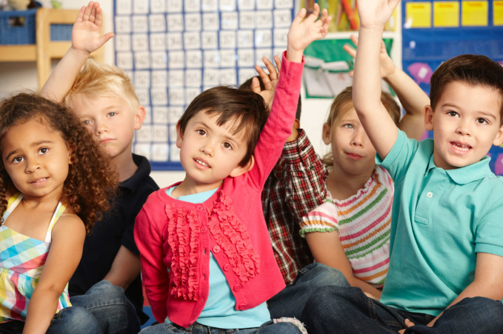Children in classroom, raising hands